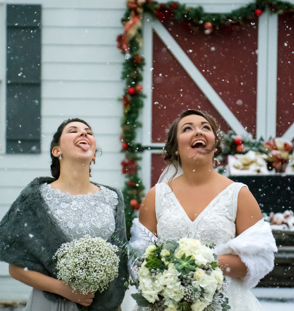 Bride and bridesmaid catching snowflakes