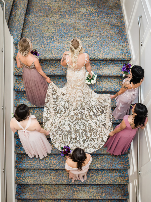 Bride with bridesmaids carrying dress train