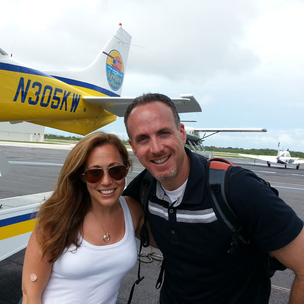 jen with her husband in front of the plane