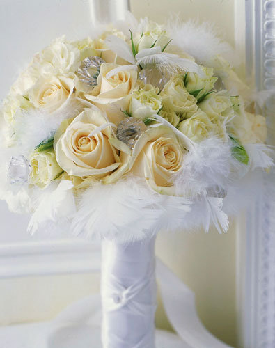 The bridal bouquet of satiny white roses glittering crystals and soft white