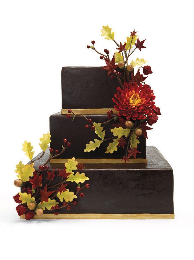 Chocolate fondantcovered wedding cake with sugarpaste red dahlia oak and