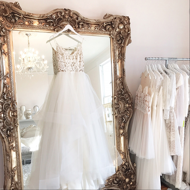hanging wedding dresses at bridal salon