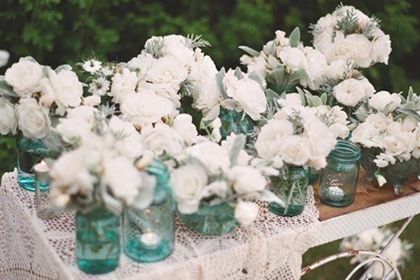 blue mason jars and white flowers