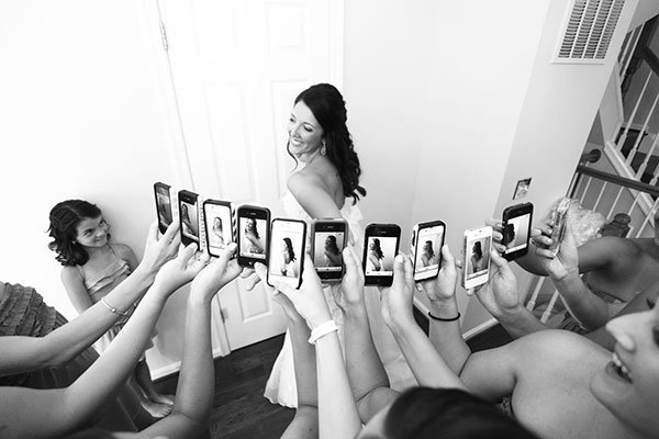bridesmaids with iphones taking picture of the bride