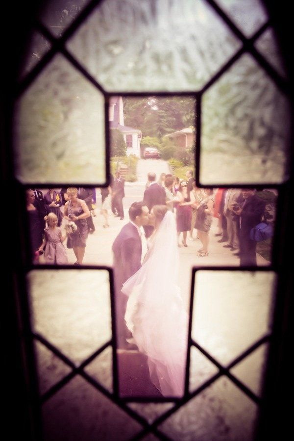 wedding photo through the church stained glass window