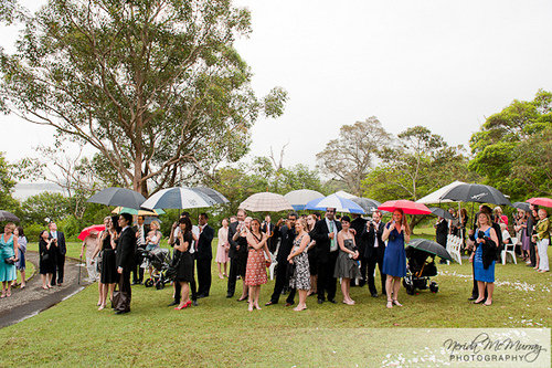 wedding guests with umbrellas