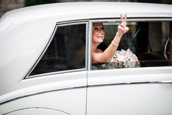 bride making peace sign out the car window