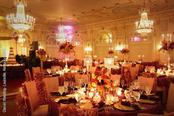 Rosecovered chairs enhance the glamour of this ballroom wedding reception