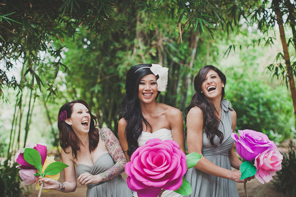 bride and bridesmaid holding giant paper flowers