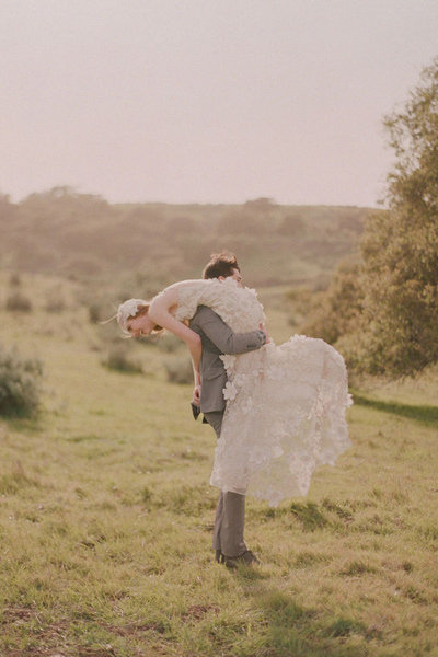 groom carrying bride over his shoulder
