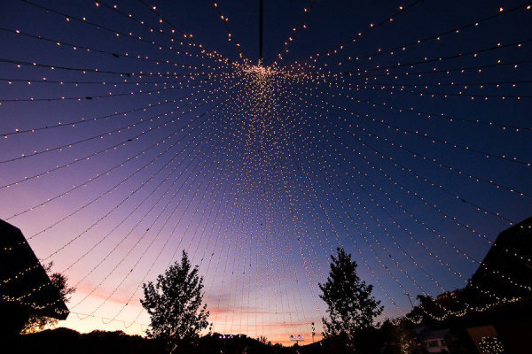 outdoor canopy of lights although outdoor weddings have different lighting needs they can be just as beautiful check out this amazing tent of lights