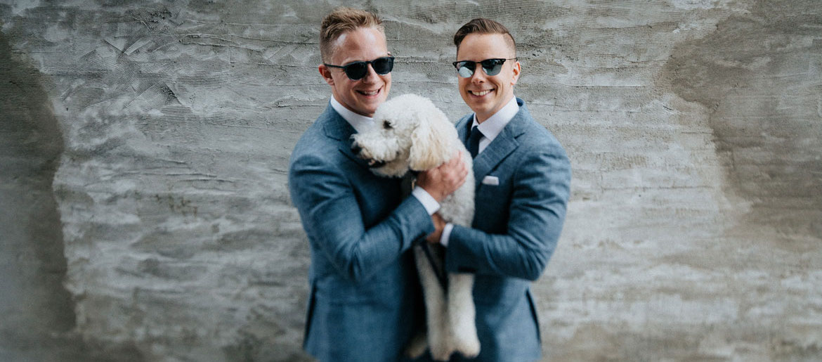 Grooms holding dog