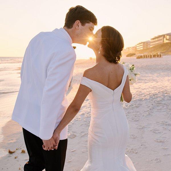 bride and groom kiss on beach