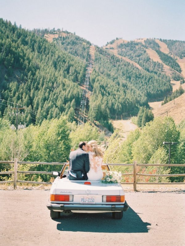 Bride and Groom sitting on car