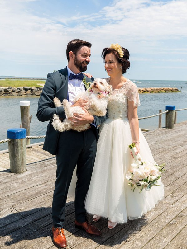 Bride and groom with dog on a pier