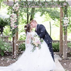 Flower petals falling around bride and groom kissing
