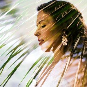 Bridal portrait through palm tree leaves