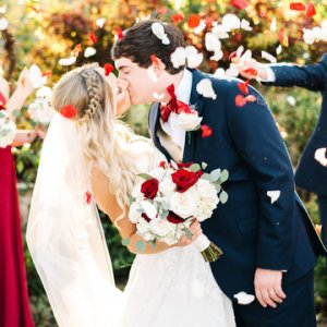 Bride and Groom Kissing Under Flower Petals